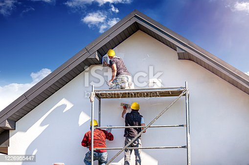 istock Construction workers plasters the building facade. 1226955447
