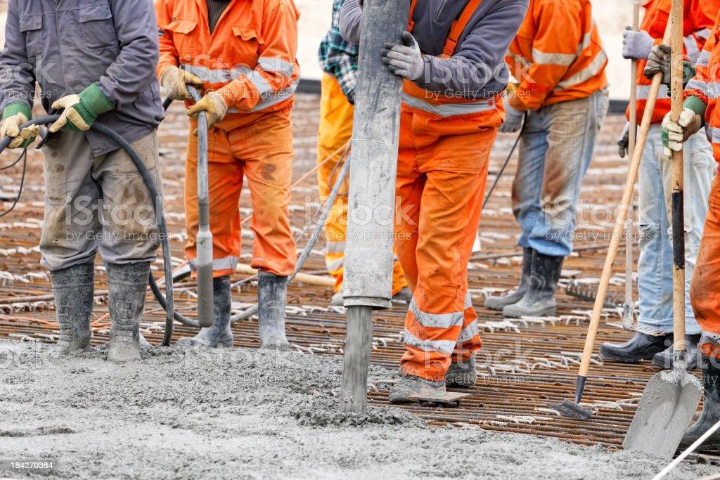 Construction workers pour concrete stock photo
