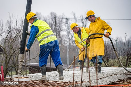 istock Construction workers pouring cement on roof 1070008336