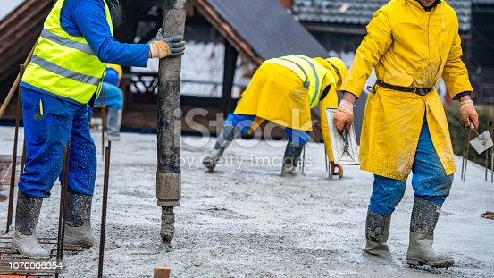 istock Construction workers pouring cement on roof 1070008354