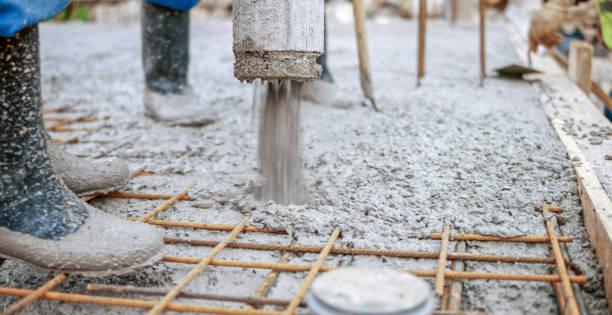 operai edili che versano cemento sul tetto - calcestruzzo foto e immagini stock