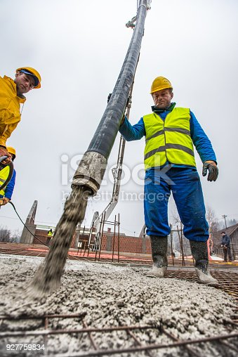 istock Construction workers pouring cement on roof 927759834