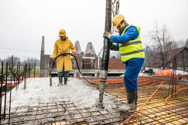 bauarbeiter gießen zement auf dach - betonbau stock-fotos und bilder