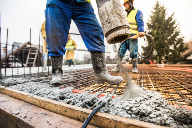Construction workers pouring cement on roof Manual workers pouring cement through pipe on roof. cement stock pictures, royalty-free photos & images