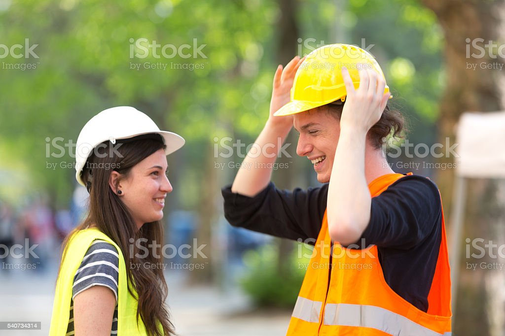Two construction workers, a boy and a girl, putting on their...