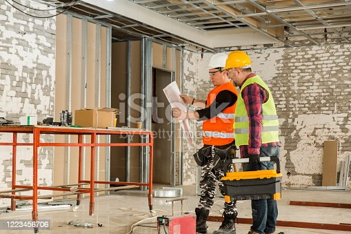521012560 istock photo Construction workers reading blueprints. 1223456706