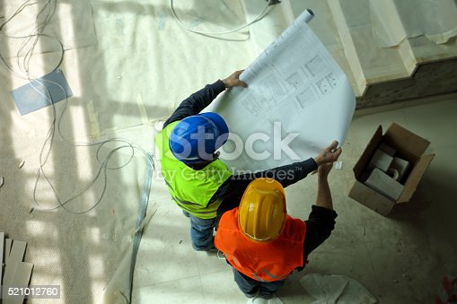 521012560 istock photo Construction workers reading blueprints 521012760