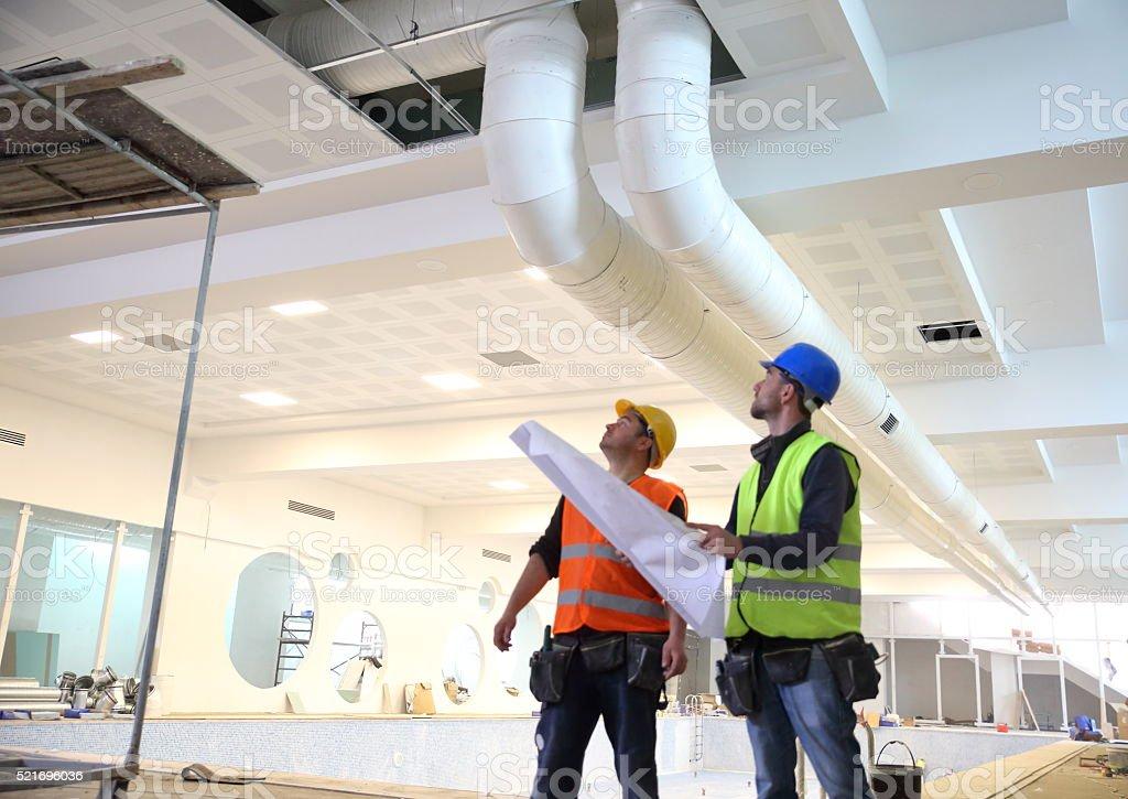 Bau Arbeiter lesen Pläne liegen vor Lizenzfreies stock-foto