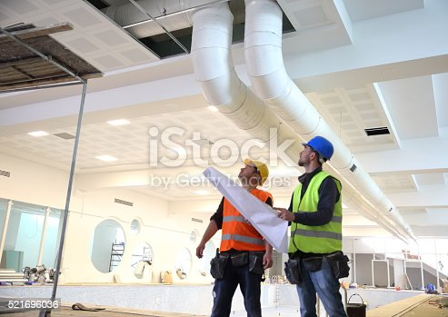 istock Construction workers reading blueprints 521696036