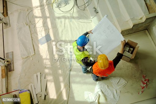 istock Construction workers reading blueprints 623667028