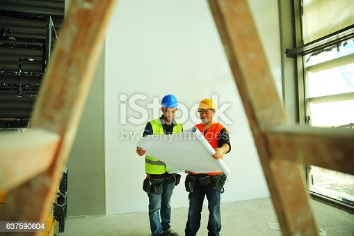 521012560istockphoto Construction workers reading blueprints 637590604