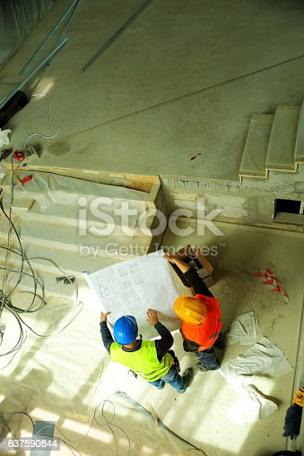 521012560 istock photo Construction workers reading blueprints 637590844