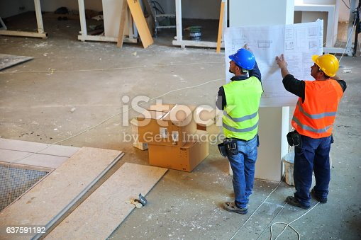 521012560 istock photo Construction workers reading blueprints 637591192
