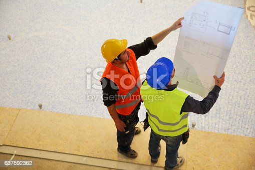 521012560 istock photo Construction workers reading blueprints 637592362