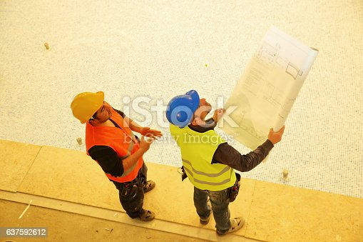521012560 istock photo Construction workers reading blueprints 637592612