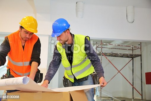 521012560 istock photo Construction workers reading blueprints 643130058