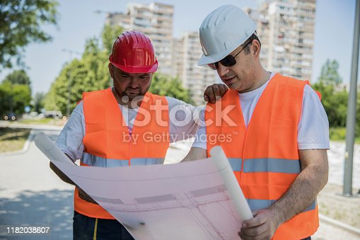 Construction workers wearing fluorescent vests reading documents on their place of work