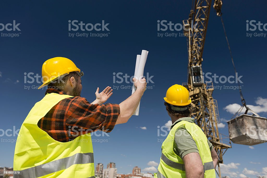Construction workers signaling to crane operator stock photo