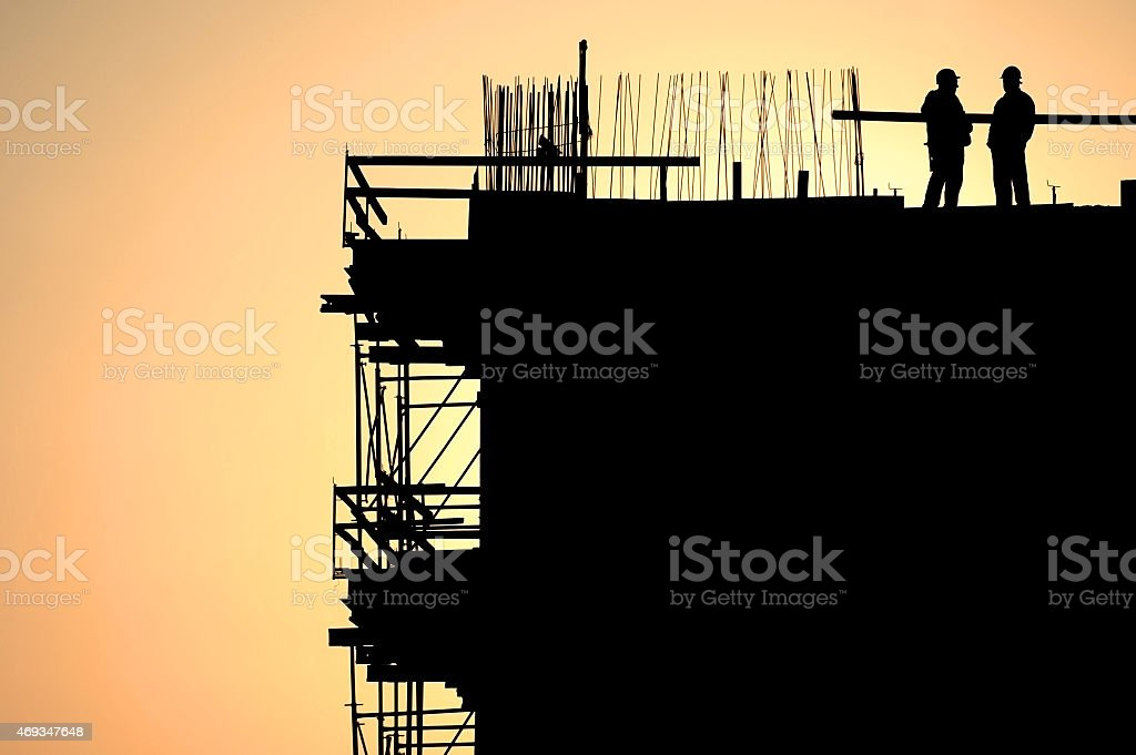 Construction workers silhouettes at sunset stock photo