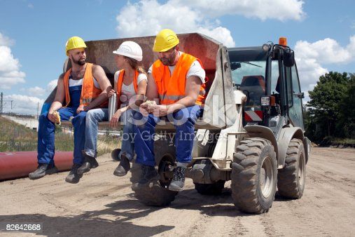 istock 3 construction workers sitting on machinery 82642668