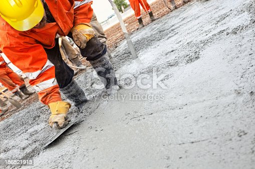 Construction workers smooth the concrete.