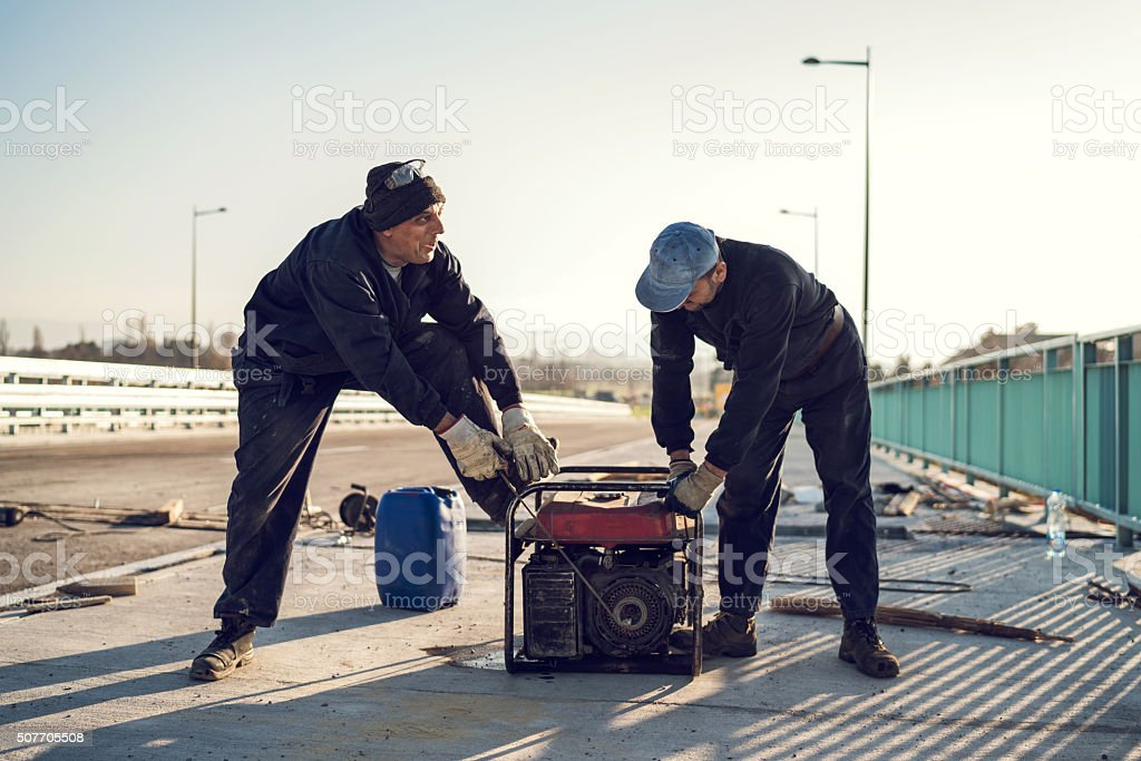 Construction workers starting power generator on the bridge. stock photo