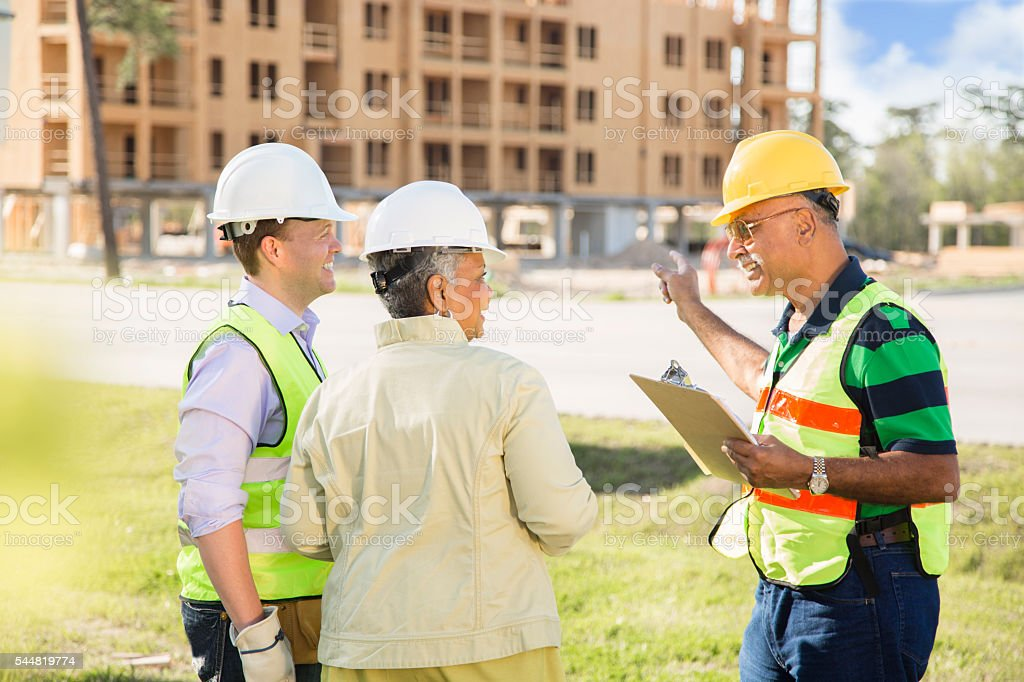 Construction workers, supervisor, engineer talk at job site. stock photo