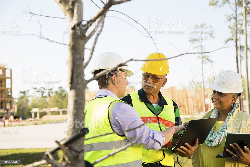 Construction workers, supervisors talk at job site. Technology. stock photo