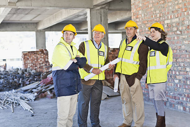 construction workers talking on site - four people stock photos and pictures