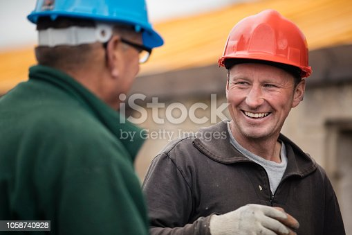 Over the shoulder view of two construction workers talking and laughing outdoors. They are both wearing protective hardhats.