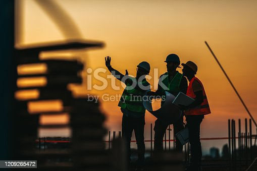 Silhouette Successful male engineer standing survey work on construction