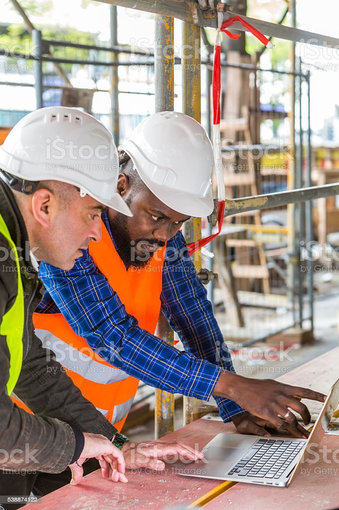 Construction workers using laptop computer among scaffolding – Foto