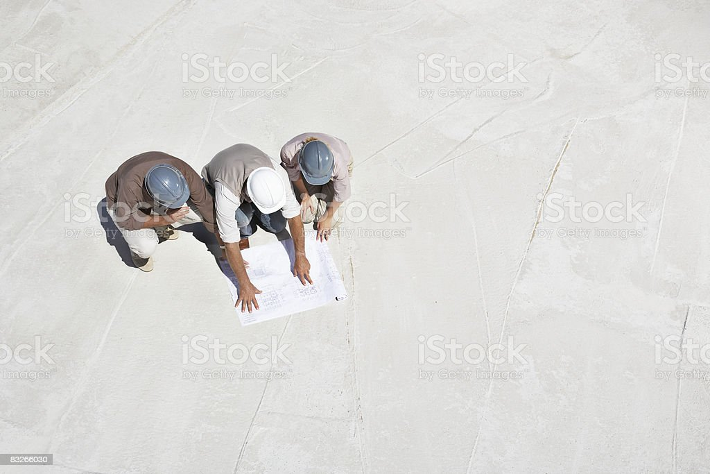 Construction workers viewing blueprints on construction site royaltyfri bildbanksbilder