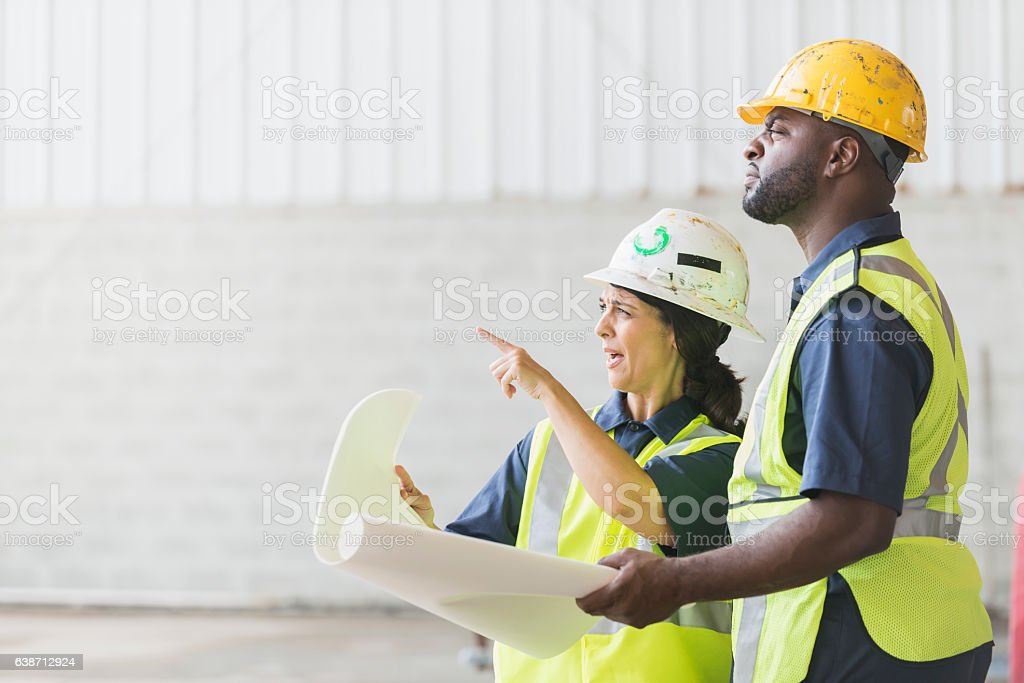 Construction workers with hardhats and blueprints stock photo