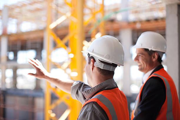 pracowników budowlanych w pracy na plac budowy - kask ochronny odzież ochronna zdjęcia i obrazy z banku zdjęć