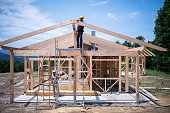 Builders working on wooden construction site, modern wooden house.