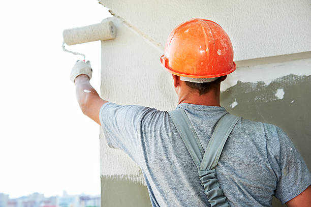 Construction working putting plaster on a wall stock photo