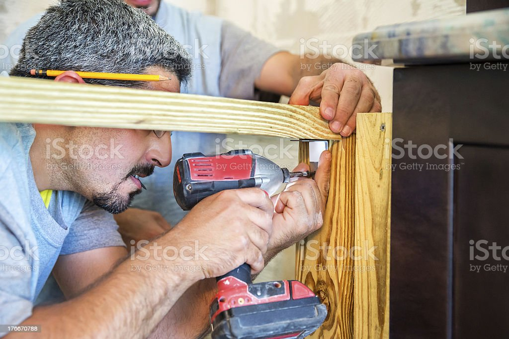 Construction: Workmen drilling screw into a piece of wood royalty-free stock photo