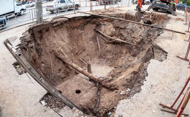 Bauarbeiten an rostigen Eisenrohren in einer Tiefe des ausgehobenen Grabens – Foto