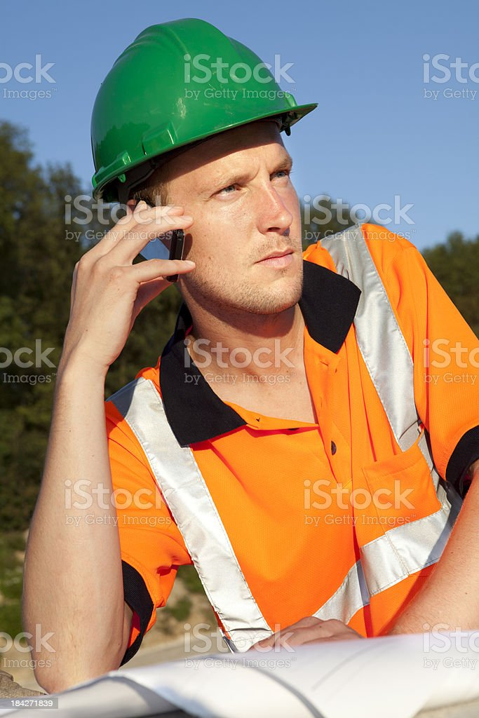 Constructionworker looking on blueprint and calling the foreman for help. royalty-free stock photo