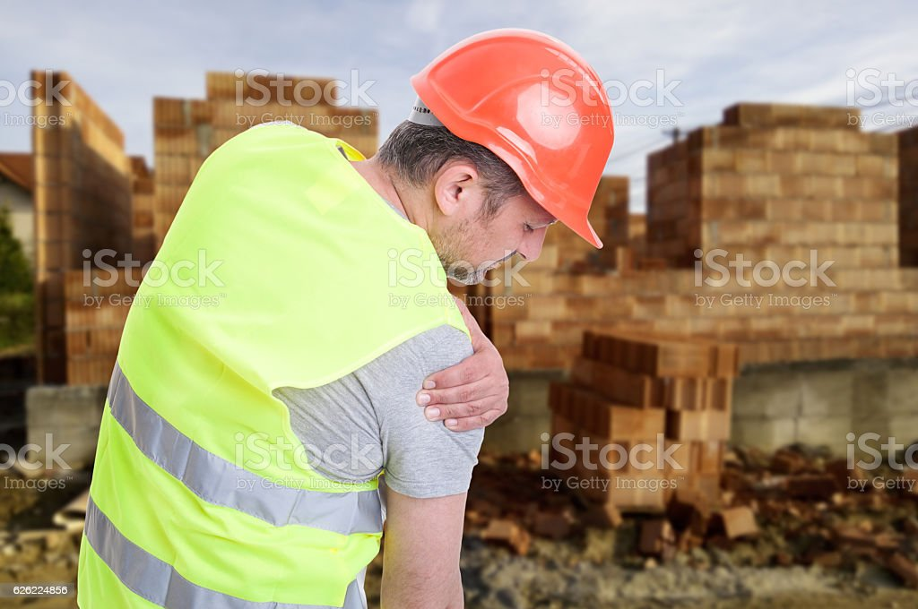 Constructor suffering from shoulder pain stock photo