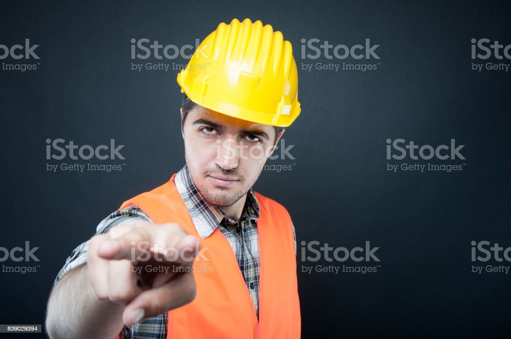 Constructor wearing equipment making watching you gesture stock photo