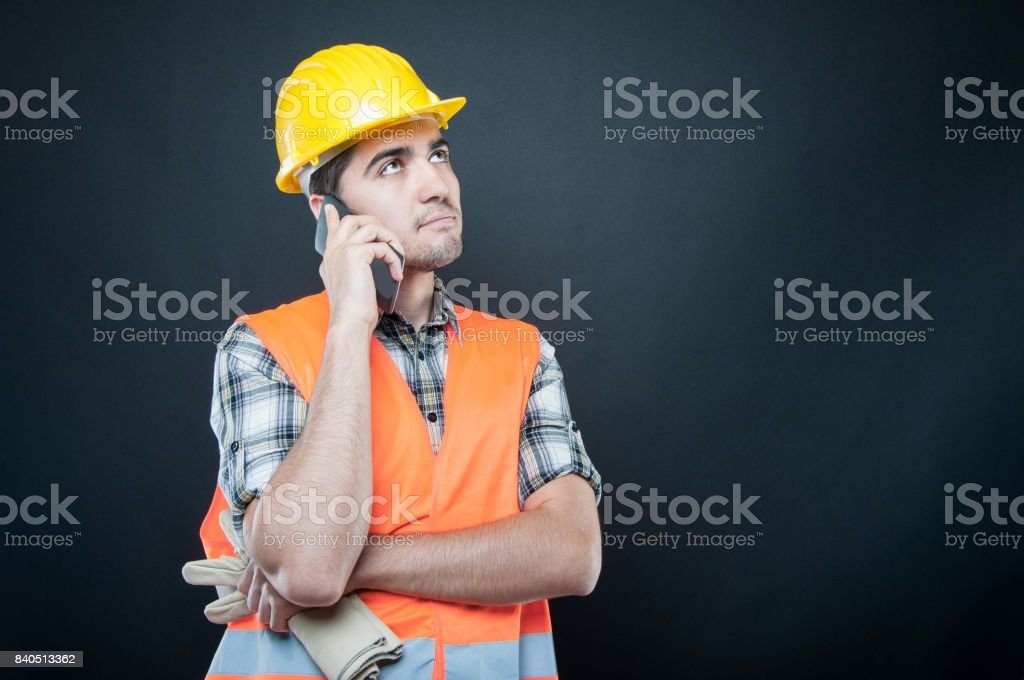 Constructor wearing equipment talking on phone holding gloves stock photo