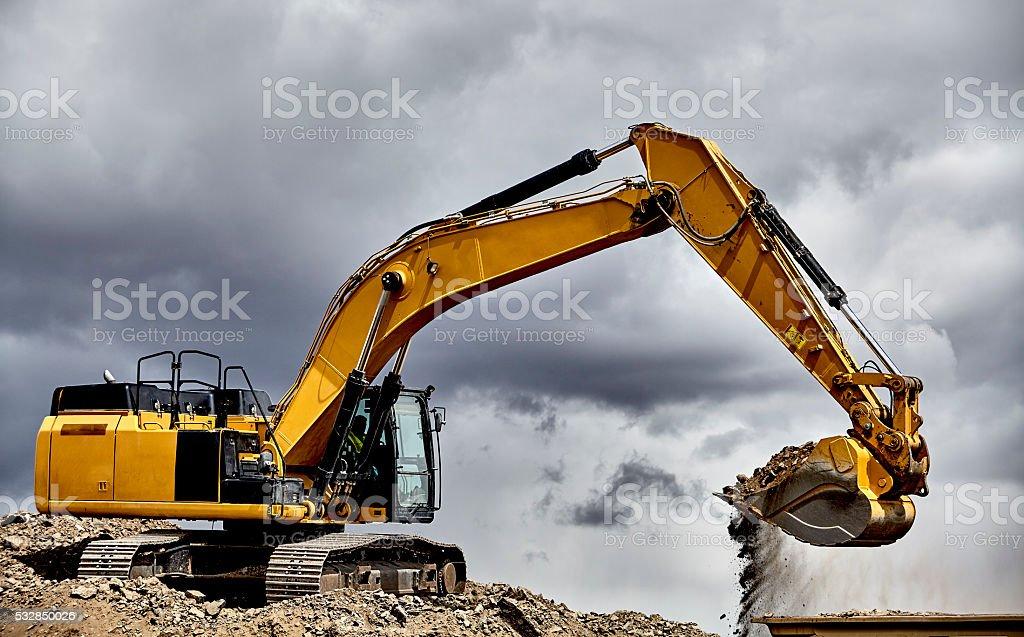 Constuction industry heavy equipment excavator loading gravel stock photo