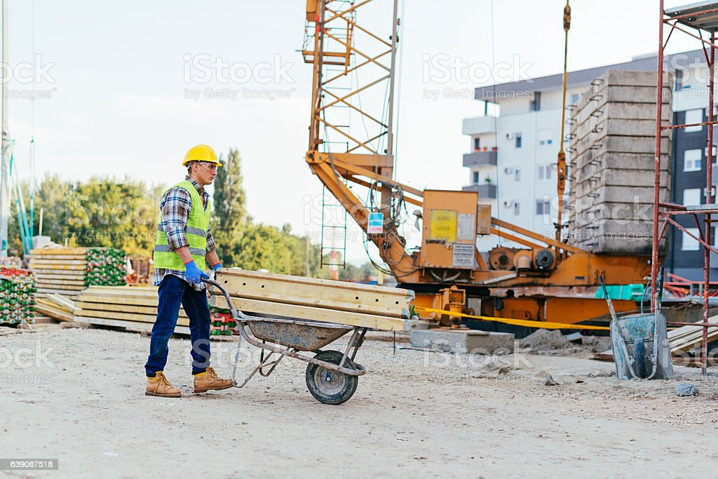 Consturction worker pushing wheelbarrow on construction site stock photo