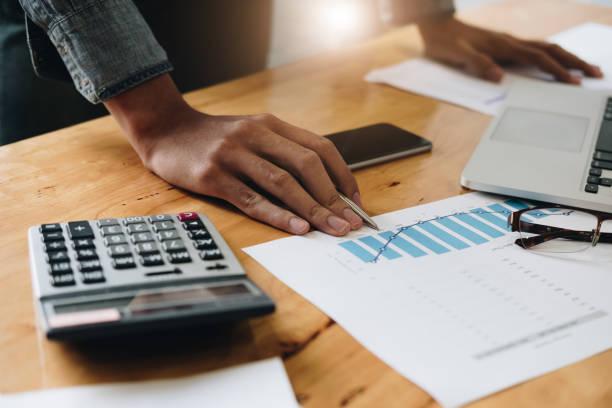 Konsultieren Sie das Finanzkonzept. Geschäftsmann, der auf Papwerarbeit zeigt und Laptop-Computer benutzt. – Foto