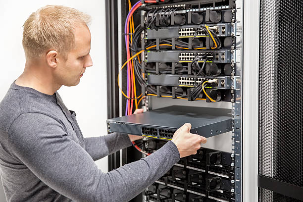 IT consultant build network racks in datacenter stock photo