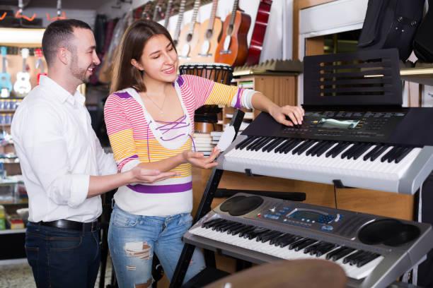 berater helfen mann synthesizern auswählen - klavier verkaufen stock-fotos und bilder