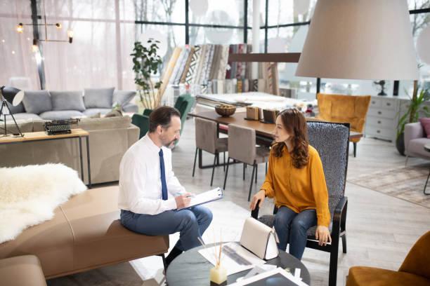 Berater in Krawatte und weißem Hemd erklärt Diskussionsauftrag mit dem Kunden – Foto