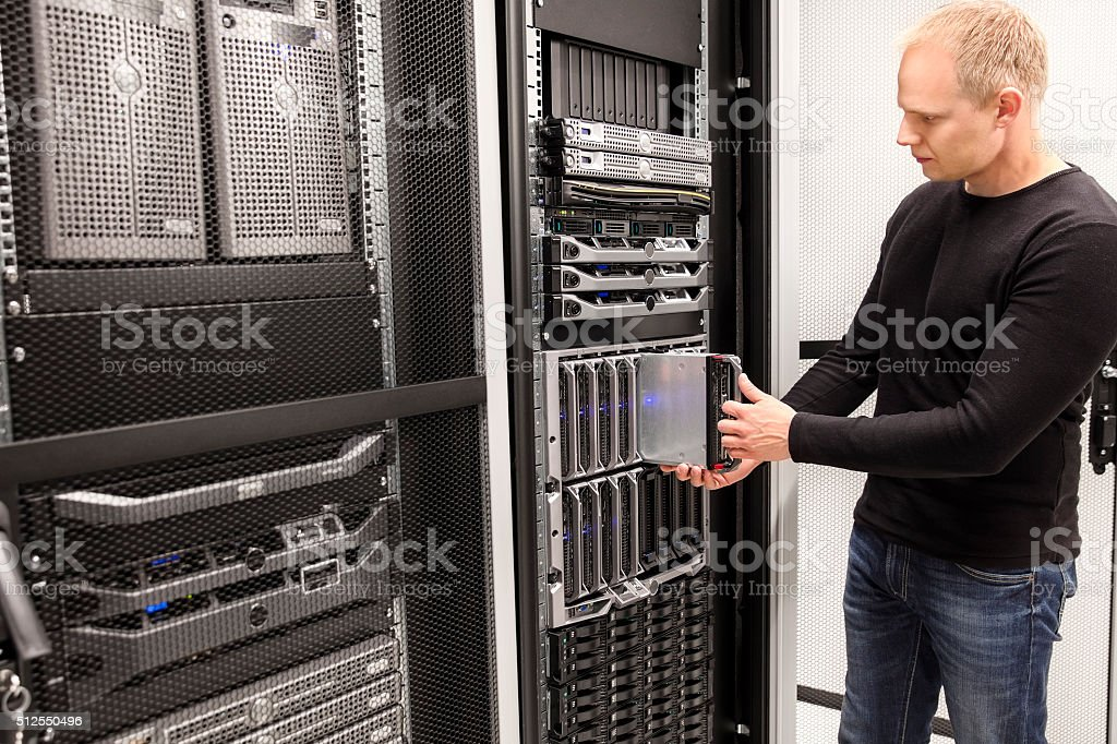 IT Consultant install blade server in large datacenter stock photo